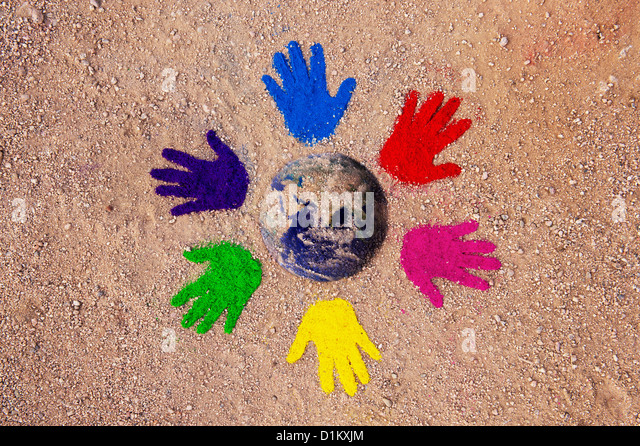 Coloured powder hand prints in a circular pattern on a dirt track with the earth composited in the middle - Stock Image