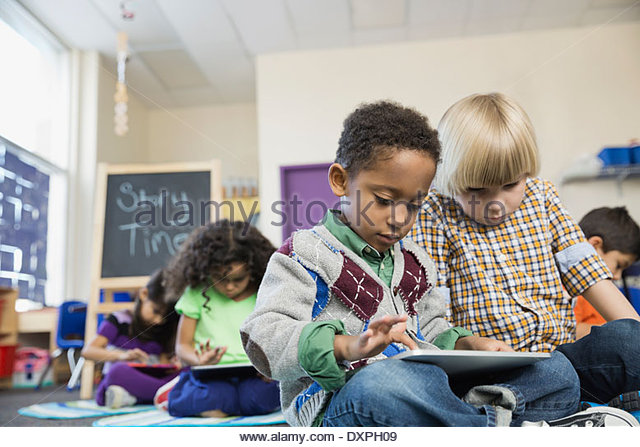 Boys using digital tablet together in elementary school - Stock Image