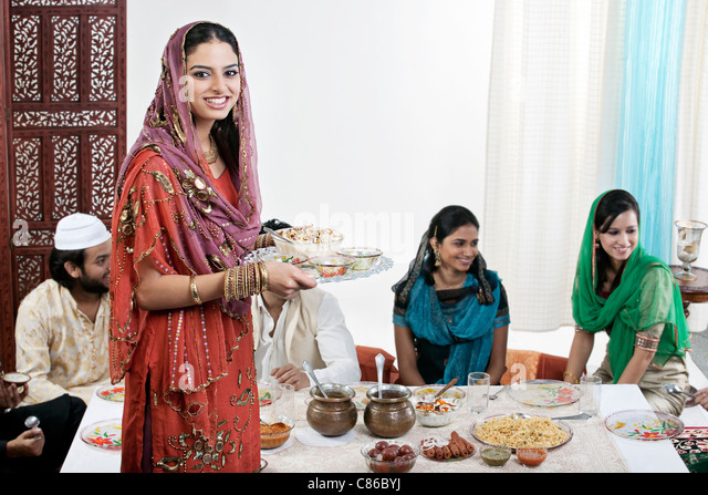 Muslim woman serving food during Id - Stock Image