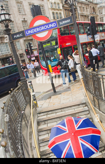 Piccadilly Circus Tube exit with a woman walking up the stairs with a Union Jack umbrella - Stock Image