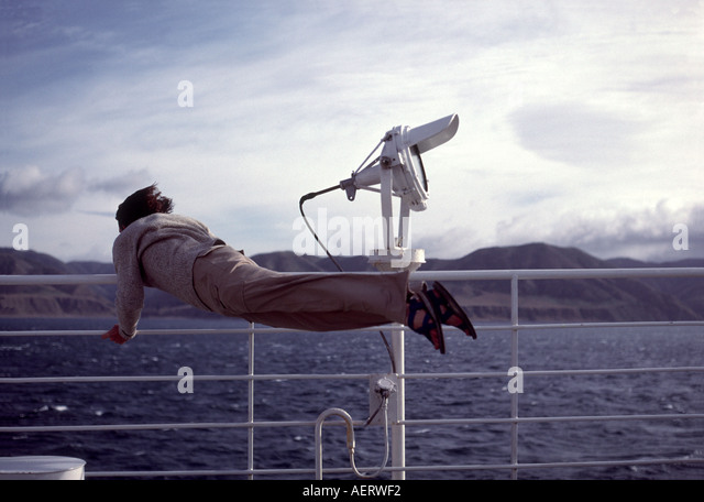 Man holding on to rail being blown by high winds on ship deck - Stock Image
