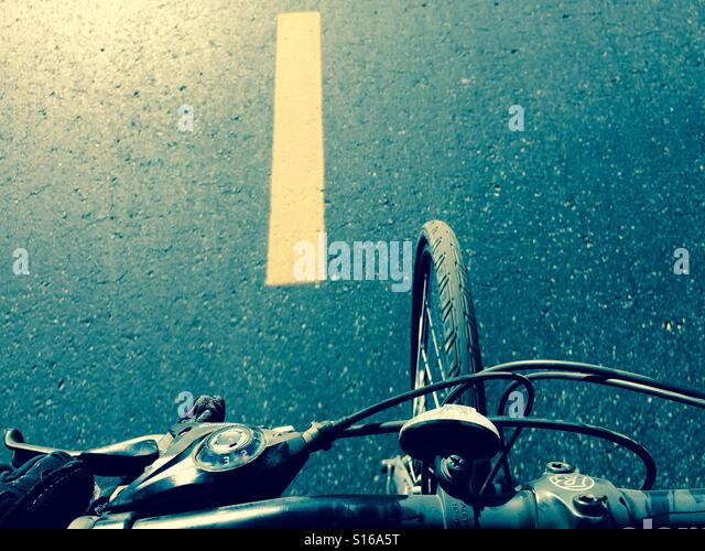 Riding a bicycle on a paved road; view from the handlebars - Stock-Bilder