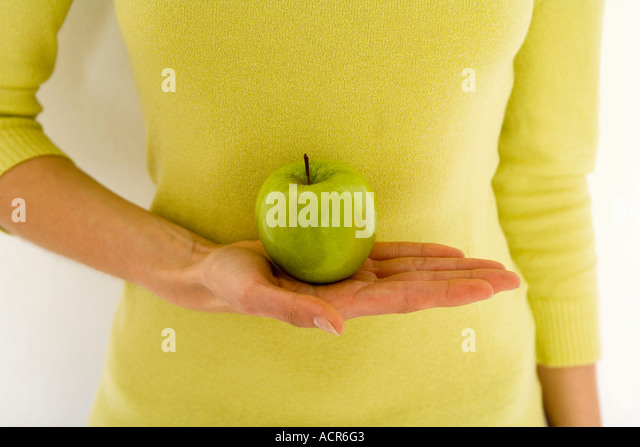 Woman holding green apple - Stock Image