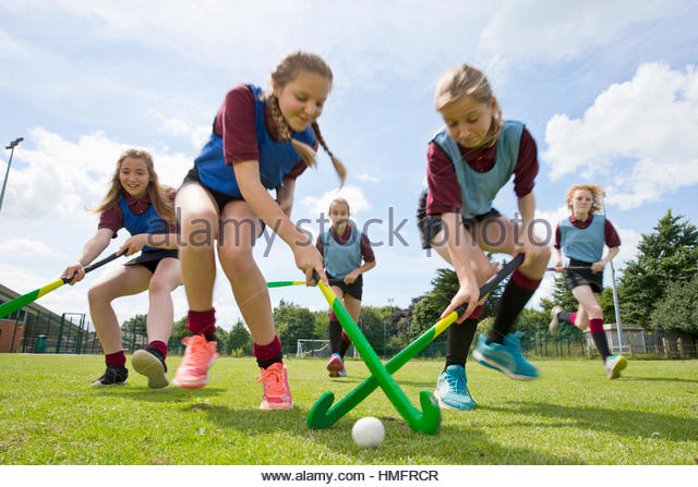 Middle schoolgirls playing field hockey in physical education class - Stock-Bilder