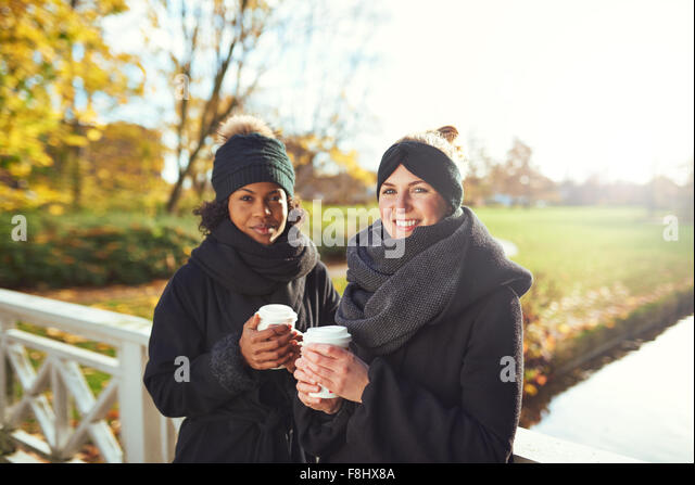 Two young women standing on bridge and holding coffee to go, smiling - Stock Image