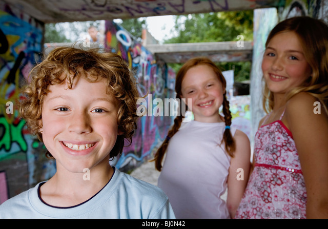 portrait of three young children at playground - Stock Image