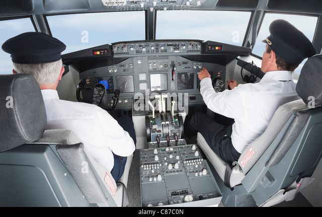 Germany, Bavaria, Munich, Pilot and co-pilot piloting aeroplane from airplane cockpit - Stock Image
