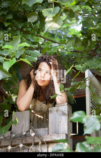 Woman peering out of tree house - Stock Image