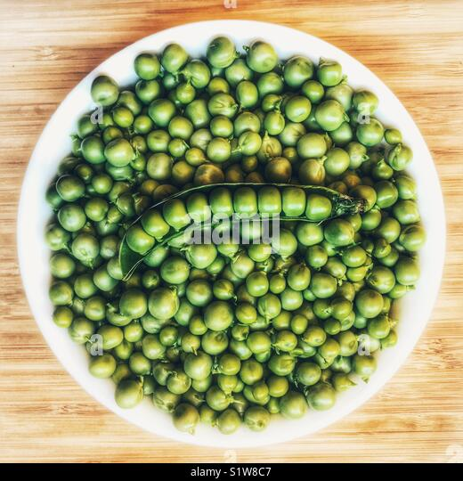 Bowl of fresh garden peas, and peas in a pod, high angle view - Stock Image