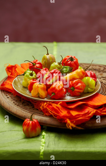 A plate of Scotch bonnet peppers on a carved wooden board - Stock Image