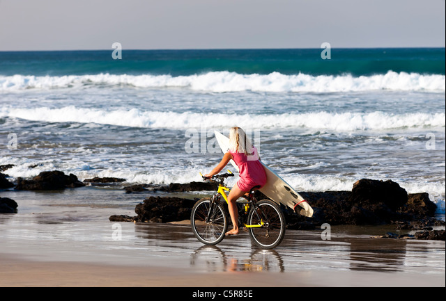 A blond surfer girl rides along beach to the waves. - Stock-Bilder