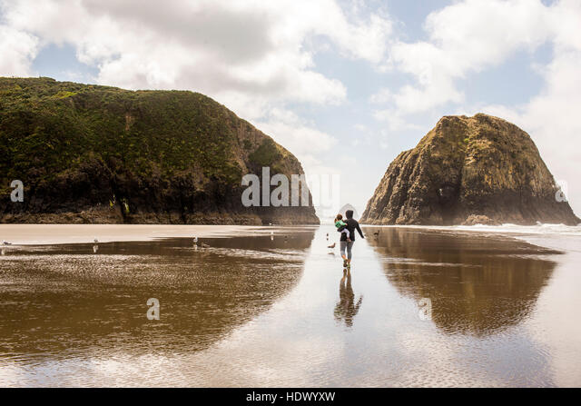 Caucasian mother carrying daughter on beach - Stock Image