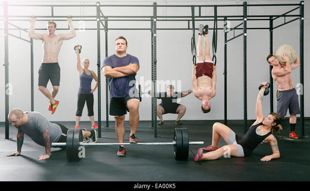 Portrait of eight men and women active in gym - Stock Image