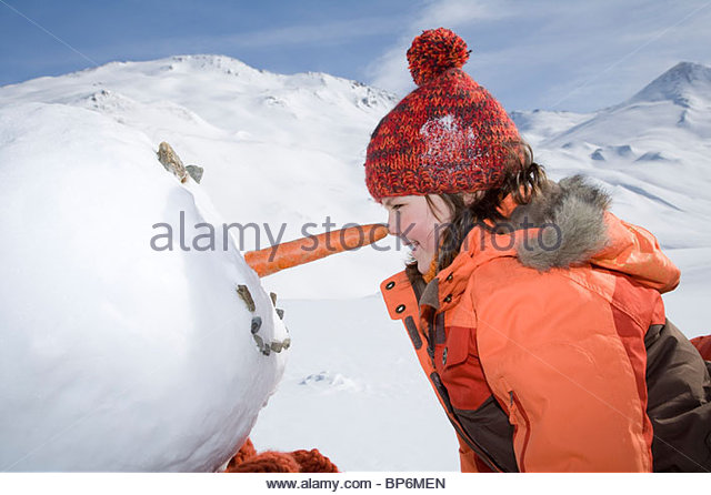 Young girl rubbing nose against snowman with a carrot nose - Stock Image