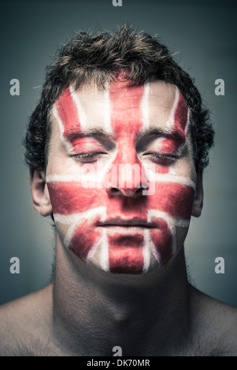 Portrait of man with British flag painted on his face and closed eyes. - Stock Image