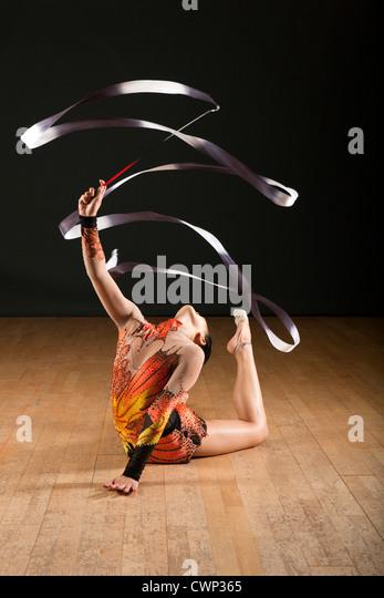 Gymnast bending backwards on floor, twirling ribbon - Stock Image