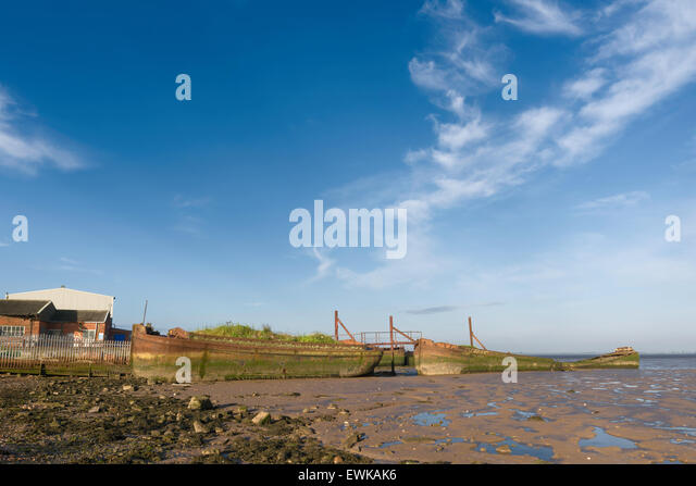 Derelict, rusting ships beached in the mud flats of the Humber estuary next to a disused ship yard at dawn. - Stock Image