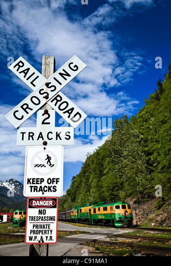 White Pass & Yukon Route Railway Train at a railroad crossing, Skagway, Southeast Alaska, Summer - Stock Image