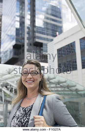 Portrait smiling businesswoman below city highrises - Stock Image