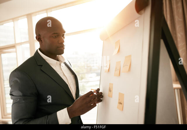African businessman standing by a whiteboard with sticky notes. Young business executive presenting his ideas on - Stock Image