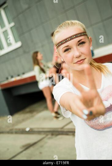 Teenage girl making peace hand sign - Stock-Bilder