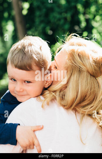 Child happily hugging mother outdoors - Stock Image