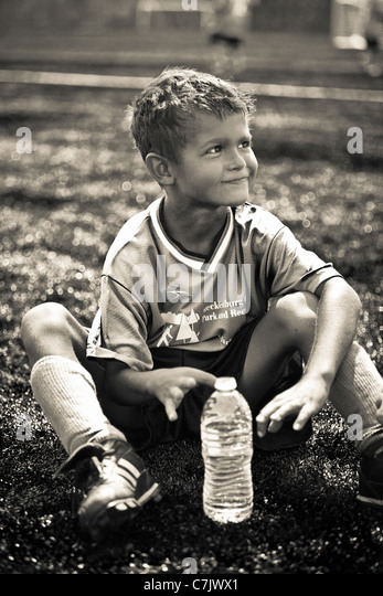 Young soccer player sitting - Stock Image