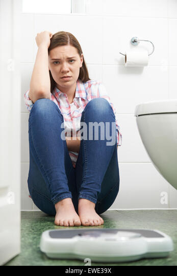 Unhappy Teenage Girl Looking At Bathroom Scales - Stock Image