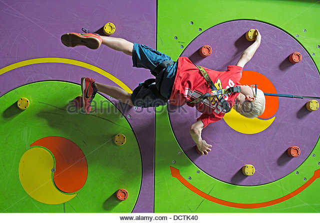 young person using an indoor climbing wall. - Stock Image