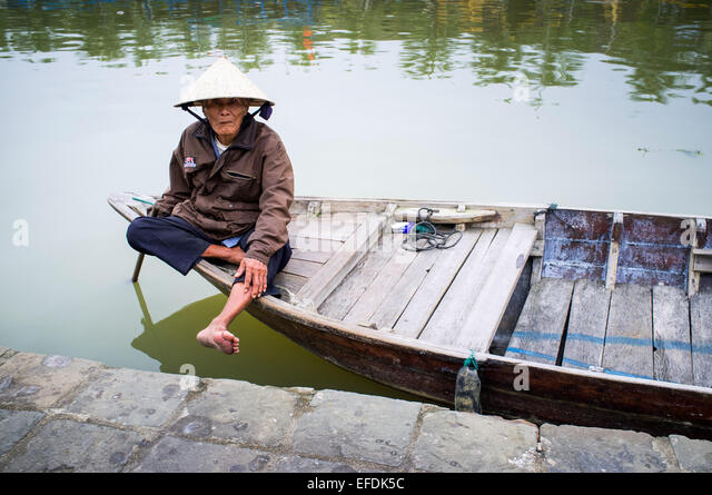 Local man with conical hat in boat, Hoi An, Vietnam, Asia. - Stock Image