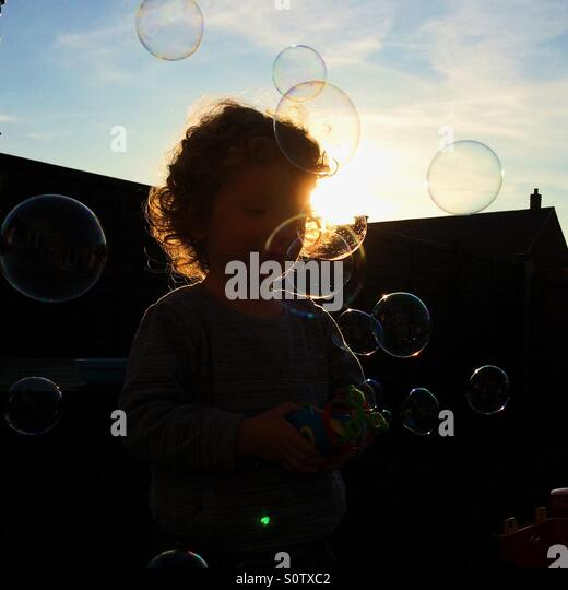 Silhouetted child playing with bubbles in garden - Stock-Bilder