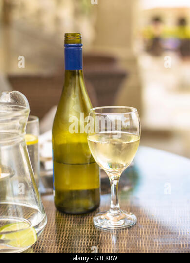 Bottle of Half Empty White Wine on a Wicker Table with a Glass and Jug of Water - Stock Image