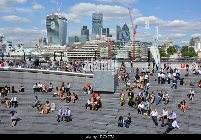 Office workers at lunch time sitting on the steps of The Scoop with City of London skyline beyond - Stock Image