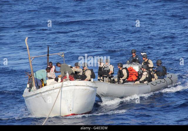 A visit, board, search and seizure team assist stranded Somali fishermen. - Stock Image