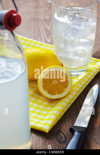 Still life photo of old fashioned or traditional homemade still lemonade with cut lemons and yellow napkin.. - Stock Image