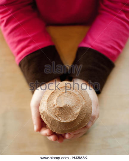 Child holding a cupcake - Stock Image