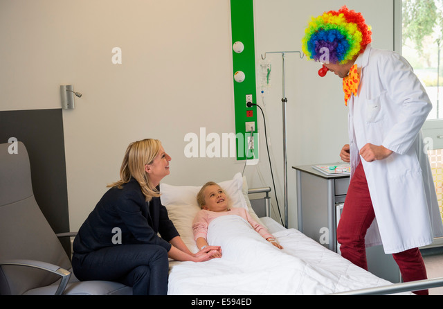 Male doctor wearing clown costume making girl patient laugh in hospital bed - Stock Image