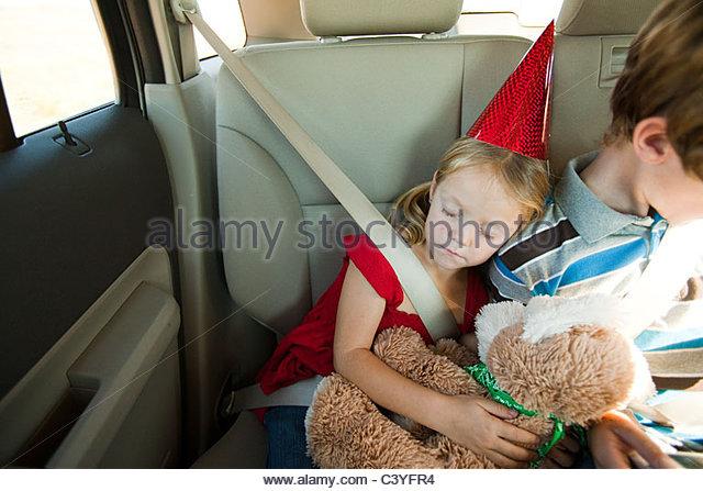 Two children in back seat of car, girl asleep - Stock-Bilder