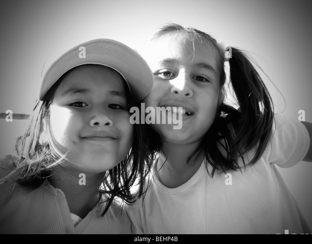 Girls sitting on baseball stands, black and white - Stock-Bilder