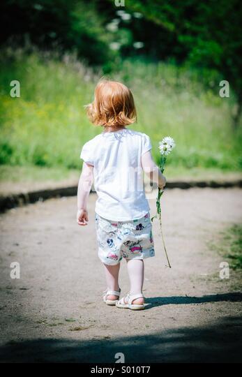 Red haired girl walking away in sun holding a daisy - Stock-Bilder