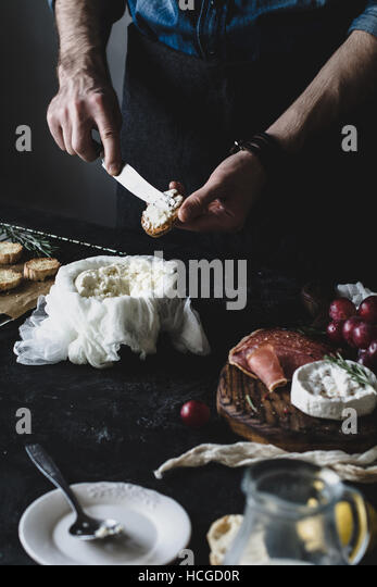 Chef prepares crostini with fresh cheese for a wine dinner or party. Selective focus, desaturated effect, toned - Stock Image