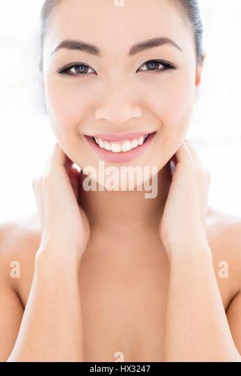 MODEL RELEASED. Young Asian woman with hands touching neck, portrait. - Stock-Bilder