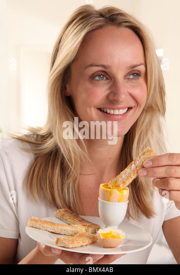 WOMAN EATING A BOILED EGG - Stock Image