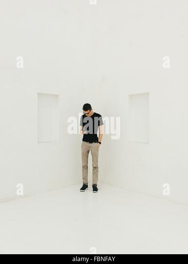 Man Using Phone While Standing In Corner Of White Room - Stock Image