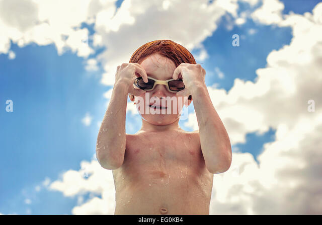 Portrait of a boy adjusting his swimming goggles - Stock Image