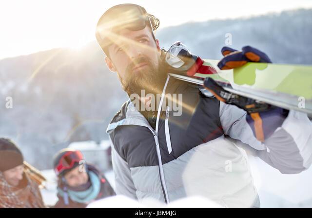 Male skier carrying skis in sunny field - Stock-Bilder