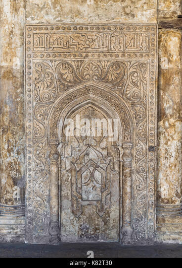 Ornate engraved stone wall with floral patterns and calligraphy at Ibn Tulun Mosque, Cairo, Egypt - Stock Image