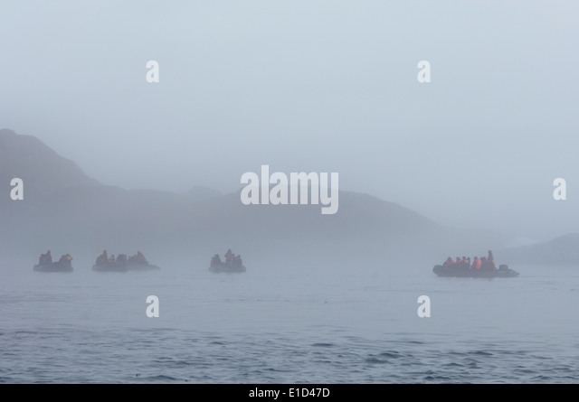 Zodiac boats with people, traveling along the cliffs in Nunavut, Canada - Stock-Bilder