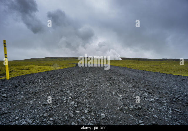 Iceland - Lonely road to geothermal energy and green moss lava field - Stock Image