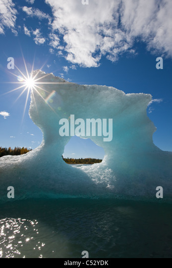 Sunny view of an iceberg in Mendenhall Lake with the sun shining from behind, Southeast Alaska, Summer - Stock Image
